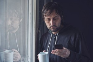 a man by the window checking his phone email with a cup in his hand